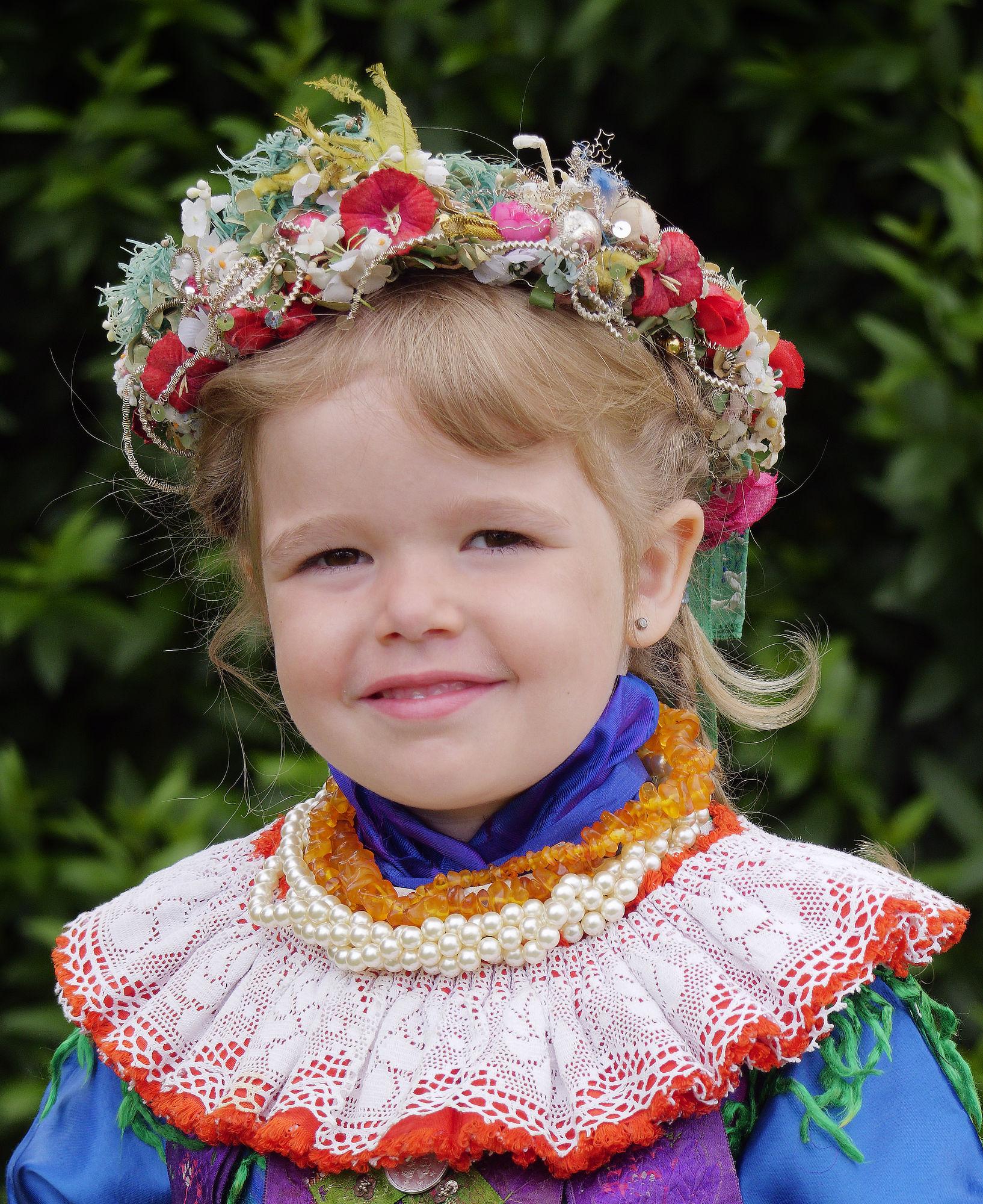 Das kleine Brautmädchen trägt auf dem Kopf ein Kränzchen, hinten mit langen Bändern.